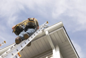Worker repairing gutters on ladder